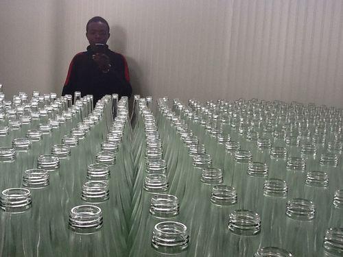 Adama evant les bouteilles vides